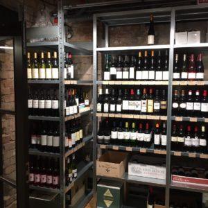 Metāla plaukti vīna pudelēm vīna veikalā